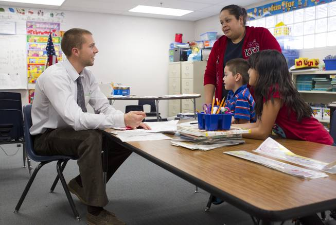 First grade teacher Charlie Lockwood talks with his student Angel Rosales, his mother Fabiola and his sister Marisol during a parent-teacher conference at Lois Craig Elementary School in North Las Vegas Wednesday, Oct. 23, 2013. Marisol helped with some translation. About 80 percent of students at the school are Hispanic.