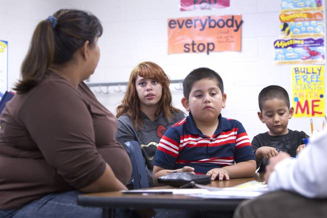 Melynda Espinoza, 15, interprets for her mother during a parent-teacher conference for her brother Miguel, center, at Lois Craig Elementary School in North Las Vegas Wednesday, Oct. 23, 2013. Another brother Christopher, 3, is at right. About 80 percent of students at the school are Hispanic.
