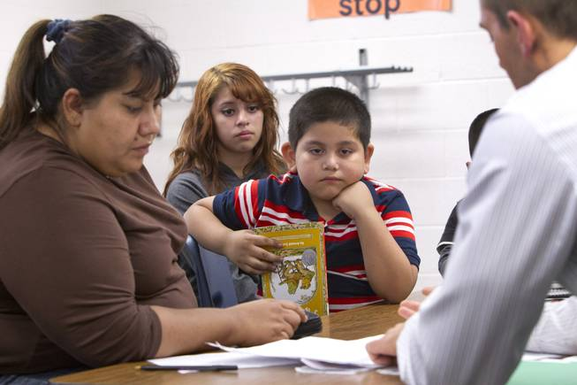 Melynda Espinoza (background),15, interprets for her mother Irene during a parent-teacher conference for her brother Miguel, center, at Lois Craig Elementary School in North Las Vegas Wednesday, Oct. 23, 2013. About 80 percent of students at the school are Hispanic.