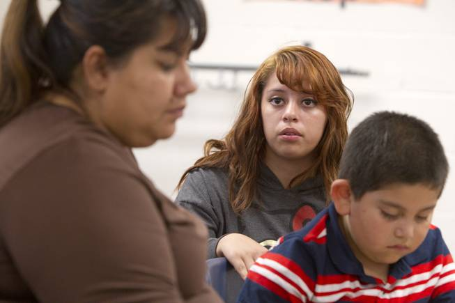 Melynda Espinoza, center,15, interprets for her mother Irene during a parent-teacher conference for her brother Miguel, center, at Lois Craig Elementary School in North Las Vegas Wednesday, Oct. 23, 2013. About 80 percent of students at the school are Hispanic.