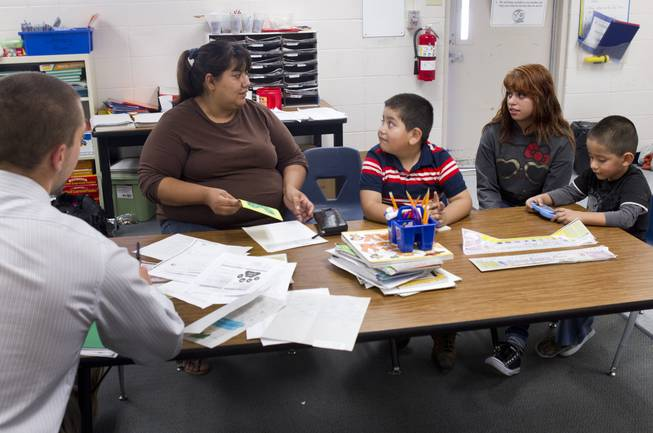Irene Garcia, left, attends a parent-teacher conference for her son Miguel, center, at Lois Craig Elementary School in North Las Vegas Wednesday, Oct. 23, 2013. Her daughter Melynda, 15, helped with the interpretation. Another son Christopher, 3, is at right. About 80 percent of students at the school are Hispanic.