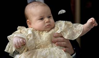 Britain's Prince George is held by his father Prince William as they arrive at Chapel Royal in St James's Palace in London, for the christening of the three month-old Prince Wednesday Oct. 23, 2013.