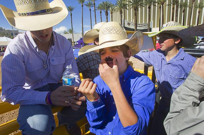 Dawson Gleaves, 12, of Amarillo, Texas applies a fake mustache before competing in the third go round of the Chris Shivers Miniature Bull Riding (MBR) World Finals at Mandalay Bay Thursday, Oct. 24, 2013. The MBR features junior riders ages 8 to11 and senior riders ages 12 to 14. The event was part of the the 2013 Professional Bull Riders Built Ford Tough World Finals.
