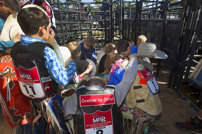 """Cowkids For Christ"" junior riders gather for a prayer before competing in the Chris Shivers Miniature Bull Riding (MBR) World Finals at Mandalay Bay Thursday, Oct. 24, 2013. The MBR features junior riders ages 8 to11 and senior riders ages 12 to 14. The event was part of the the 2013 Professional Bull Riders Built Ford Tough World Finals."