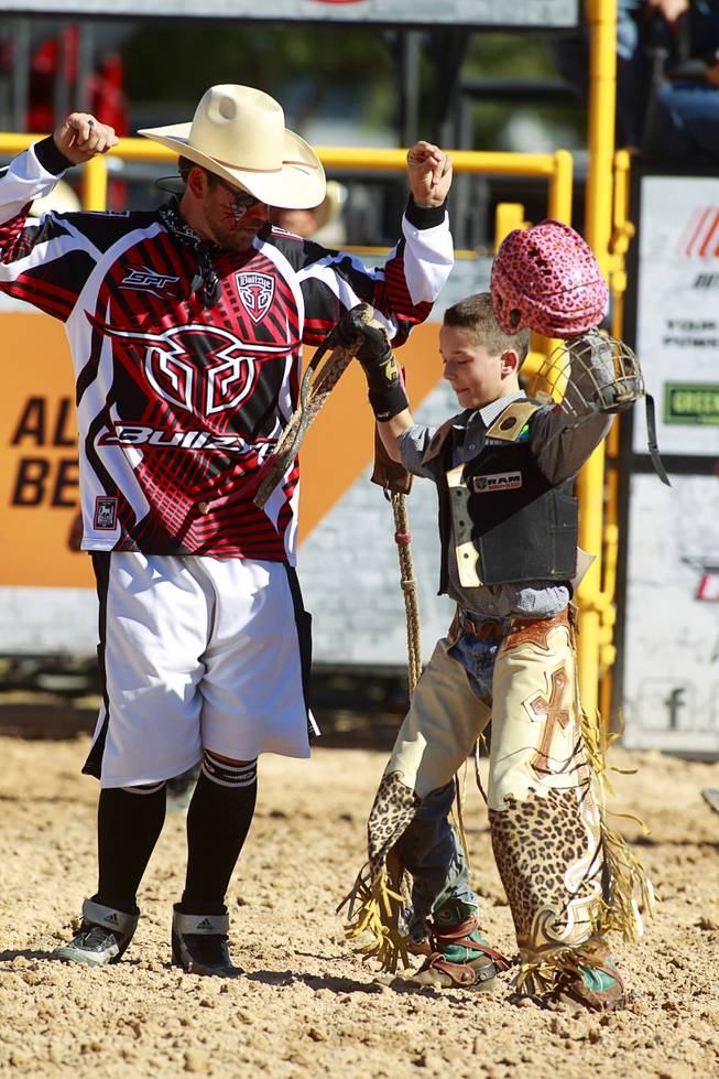 Entertainer Matt Merritt of Olin, N.C. dances with Thumper Meadows, 11, during the Chris Shivers Miniature Bull Riding (MBR) World Finals at Mandalay Bay Thursday, Oct. 24, 2013. The MBR features junior riders ages 8 to11 and senior riders ages 12 to 14. The event was part of the the 2013 Professional Bull Riders Built Ford Tough World Finals.
