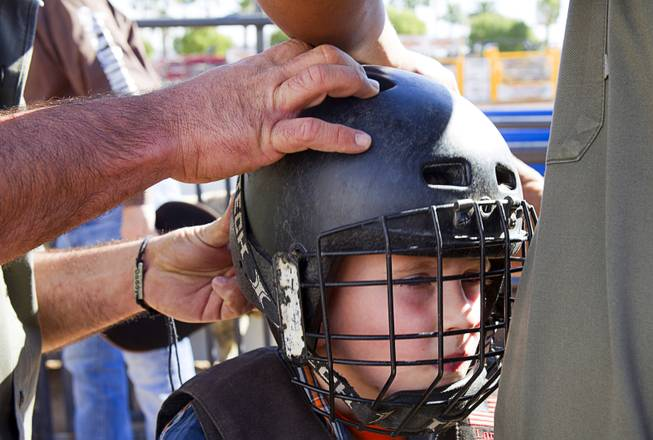 Vance Rupp, 7, of Polk City, Iowa gets fitted for a helmet before a Mutton Bustin' competition at the Tyson Fan Zone & Marketplace at Mandalay Bay Thursday, Oct. 24, 2013. Riders must be four to seven years old and weigh 60 lbs. or less. The event was part of the the 2013 Professional Bull Riders Built Ford Tough World Finals. Rupp won the morning competition.