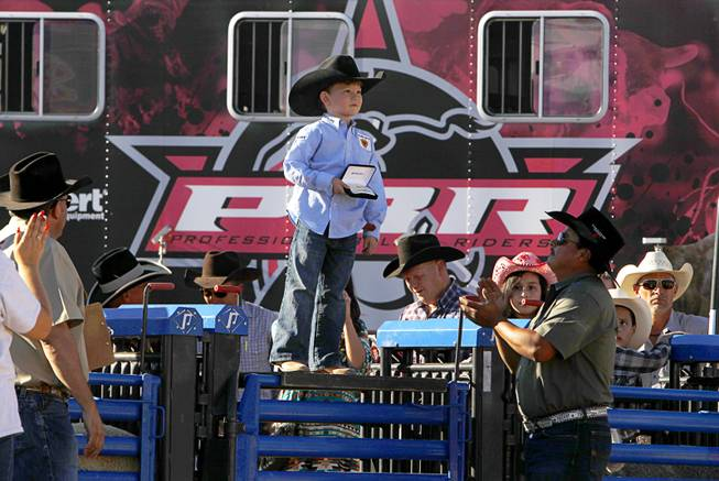 "Blayne Shivers, 6, of Jonesville, La., son of professional bull rider Chris Shivers, poses with his championship buckle after winning the afternoon Mutton Bustin"" competition at the Tyson Fan Zone & marketplace at Mandalay Bay Thursday, Oct. 24, 2013. The event was part of the the 2013 Professional Bull Riders Built Ford Tough World Finals."