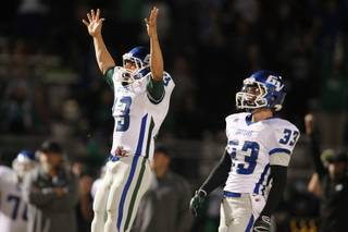 Green Valley holder Kyler Chavez signals good as kicker Conor Perkins' field goal splits the uprights during their game against Canyon Springs Thursday, Oct. 24, 2013. Green Valley won 44-43 on the last second field goal.