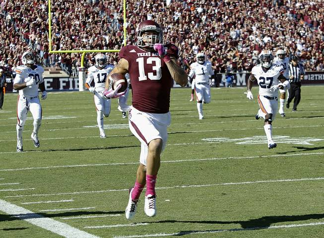 Texas A&M wide receiver Mike Evans (13) runs a 64-yard touchdown against Auburn in the first half during an NCAA college football game Saturday, Oct. 19, 2013, in College Station, Texas.