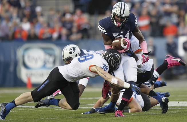 BYU's Jamaal Williams takes a hit from Boise State's Corey Bell during an NCAA college football game, Friday, Oct. 25, 2013 at LaVell Edwards Stadium in Provo, Utah.