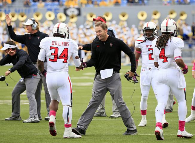 Texas Tech coach Kliff Kingsbury celebrates with Kenny Williams (34) following a touchdown run in the fourth quarter of their NCAA college football game against West Virginia in Morgantown, W.Va., on Saturday, Oct. 19, 2013. Texas Tech won 37-27.