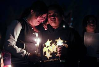 Jeannette Vasquez, 14, and Carlos Lara, 13, were among hundreds of students and residents who attended a candlelight vigil at Sparks Middle School in Sparks, Nev., on Wednesday, Oct. 23, 2013, in honor of slain teacher Michael Landsberry and two 12-year-old students who were injured after a fellow student open fire at the school on Monday, before turning the gun on himself.