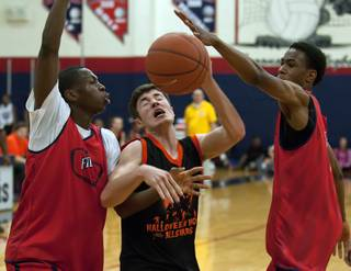 Findlay Prep players Renathan Ona Embo, left, and O'Shae Brissett converge to knock the ball away from a Halloween All-Stars player attempting to score a basket in the final seconds of a game at Coronado High School on Saturday night.