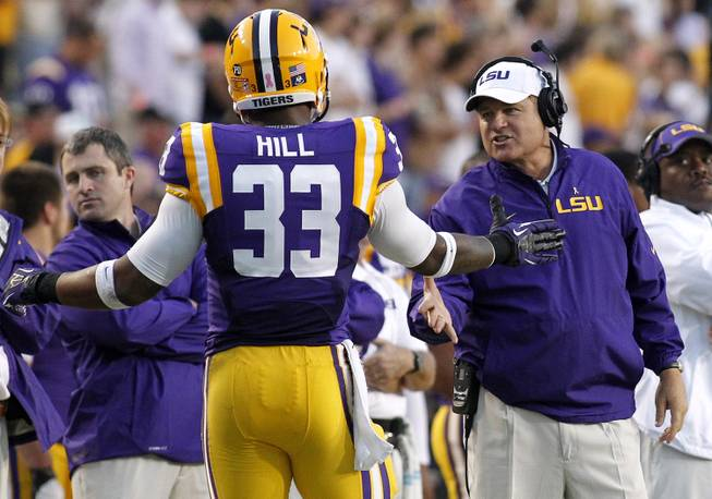 LSU head coach Les Miles congratulates running back Jeremy Hill (33) during the fist half of the NCAA college football game against Furman in Baton Rouge, La., Saturday, Oct, 26, 2013. LSU won 48-16.
