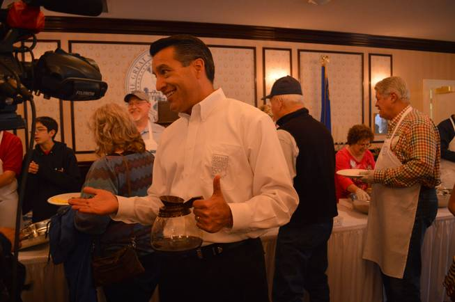 Gov. Brian Sandoval talks to a TV reporter at the annual Nevada Day pancake breakfast at the Governor's Mansion in Carson City on Saturday, Oct. 26, 2013.