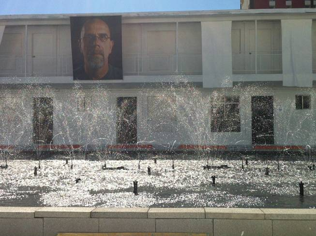 "Artist Eric Tillinghast's ""Sump Lux Fountain,"" a 30-by-60-foot reservoir in the courtyard of the Town Lodge Motel, shoots water with a Chuck Close tapestry in the background Saturday, Oct. 26, 2013."