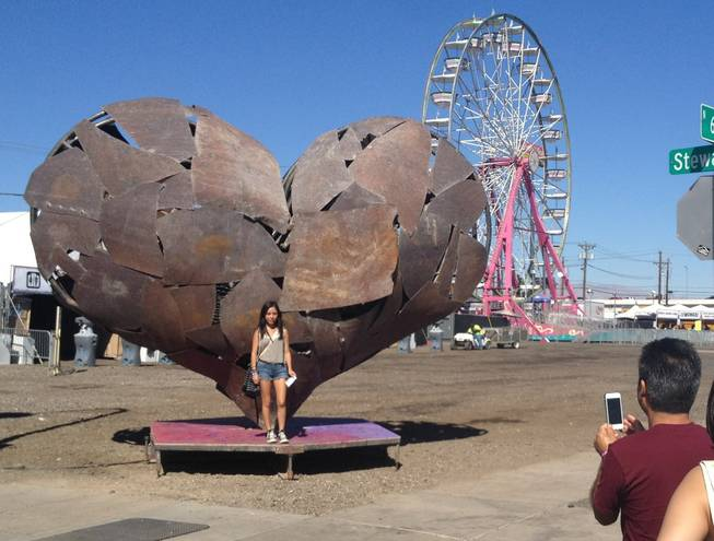 Minutes after the gates opened, people lined up for photos in front of this massive sculpture of a heart, the symbol of the Life is Beautiful festival, Saturday, Oct. 26, 2013.
