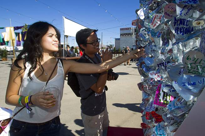 Cousins Ashley and Joey Bulosan of Las Vegas look over an art installation is shown during the Life is Beautiful Festival in downtown Las Vegas Sunday, Oct. 27, 2012. People create messages on heart-shaped, aluminum pieces that are padlocked onto the sculpture.