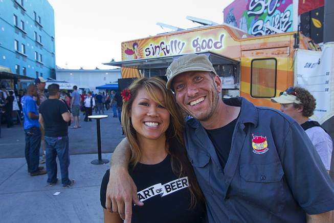 Mariann Lau poses with Tom Portnova, one of the owners of the Sin City Dogs food truck, during the Life is Beautiful Festival in downtown Las Vegas Sunday, Oct. 27, 2012.