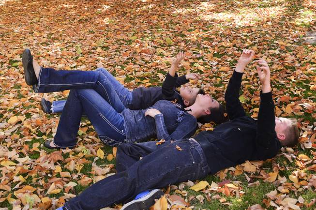 Chantelle Ewing and her sons, Shane, left, and Blake enjoy the falling leaves at the state capitol on Sunday, Oct. 27, 2013.
