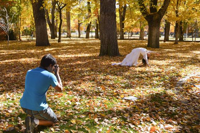 Using the falling autumn leaves on the state capitol grounds as a backdrop, Jerit Shuman photographs his mother, Lilliam, on Sunday, Oct. 27, 2013. The Shumans are from Gardnerville.