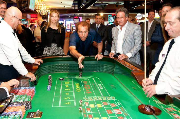 Steve Wynn rolls the dice after placing a $2,000 bet during the opening of the Downtown Grand Las Vegas Hotel and Casino on Sunday, Oct. 27, 2013.