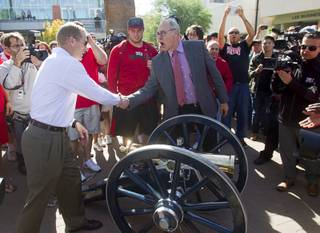 Head Football coach Bobby Hauck, left, is congratulated by UNLV President Neal Smatresk by the Fremont cannon before a painting ceremony on UNLV campus Monday, Oct. 28, 2013. The UNLV football team beat Reno Saturday 27-22 to break an eight-year losing streak in the rivalry game and gain possession of the Fremont cannon.