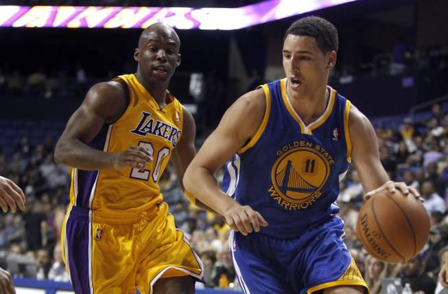 Golden State Warriors guard Klay Thompson (11) drives to the basket around Los Angeles Lakers guard Jodie Meeks (20) in an NBA basketball preseason game Saturday, Oct. 5, 2013, in Ontario, Calif.
