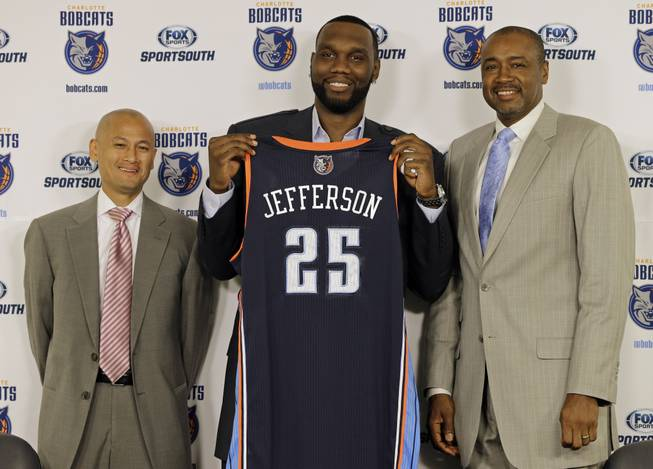 Charlotte Bobcats' Al Jefferson, center, holds up his jersey with Rod Higgins, right, president of basketball operations, and Rich Cho, left, general manager, during a news conference for the NBA basketball team in Charlotte, N.C., Wednesday, July 10, 2013. Jefferson, a free agent, signed with the Bobcats today.