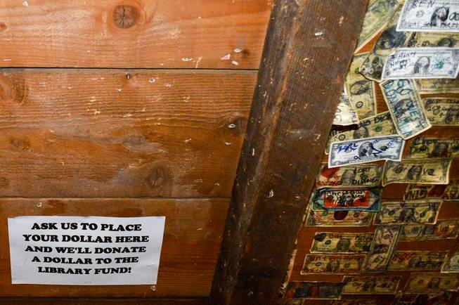 The ceiling of the bar in the Gold Hill Hotel, the oldest in the state, is usually filled with dollar bills. Late in 2013, hotel manager Clay Mitchell cleared part of the ceiling to collect money for the effort to open a new library in Virginia City.