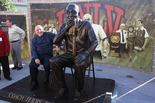 Former UNLV head basketball coach Jerry Tarkanian sits next to an oversized statue of himself after it was unveiled in front of the Thomas & Mack Center Wednesday, Oct. 30, 2013.
