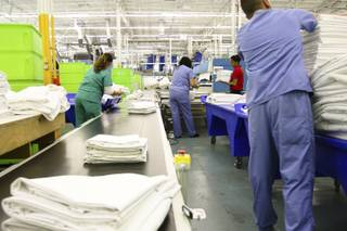 Freshly ironed and folded sheets travel along a conveyer belt as employees prepare them to be bundled for client delivery during a walk-through of Apex Linen in Las Vegas Tuesday, October 30, 2013.