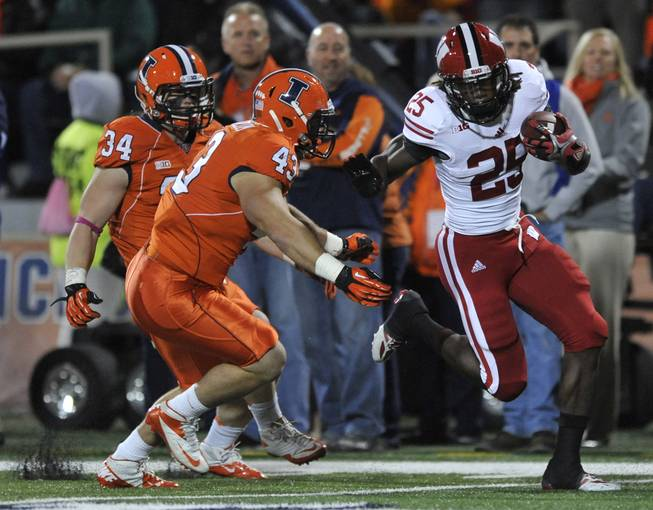 Wisconsin running back Melvin Gordon (25), rushes against Illinois' Mason Monheim (43), and Mike Svetina (34), during the first quarter of an NCAA college football game in Champaign, Ill., Saturday, Oct. 19, 2013. Wisconsin won 56-32.
