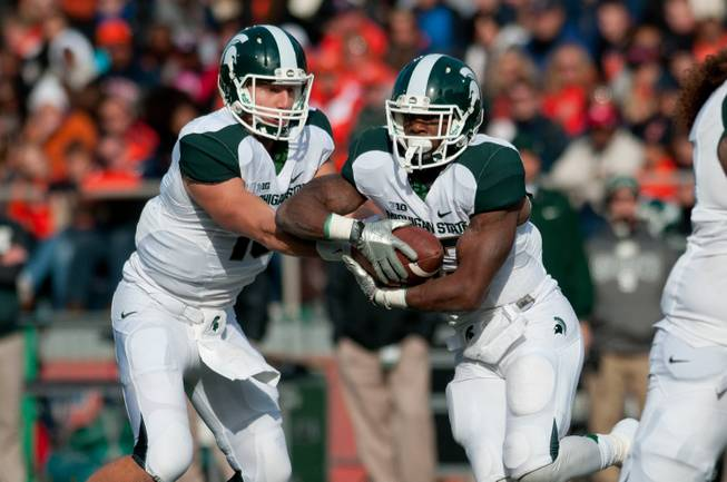 Michigan State quarterback Connor Cook hands the ball off to running back Jeremy Langford against Illinois during the first quarter of a game at Memorial Stadium in Champaign, Ill., Oct. 26, 2013.