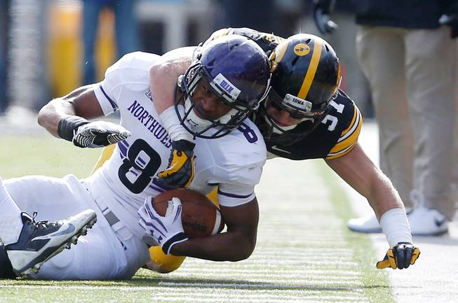 Northwestern Wildcats running back Stephen Buckley (8) is wrapped up by Iowa Hawkeyes defensive back John Lowdermilk (37) during the second half of an NCAA college football game Saturday, Oct. 26, 2013 at Kinnick Stadium in Iowa City, Iowa.