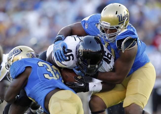 Colorado running back Christian Powell, center, is stopped by UCLA linebacker Myles Jack, left, and UCLA defensive end Keenan Graham, right, for no gain in the first half of their NCAA college football game Saturday, Nov. 2, 2013, in Pasadena, Calif.
