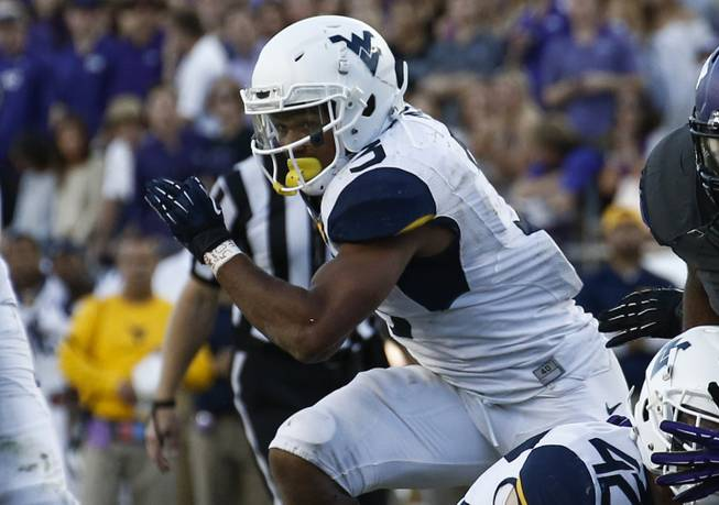 West Virginia running back Charles Sims (3) carries the ball against TCU during the second half of an NCAA football game, Saturday, Nov. 2, 2013, in Fort Worth, Texas. West Virginia won 30-27.