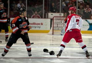 Las Vegas Wranglers forward Alexandre Mentink (7) drops his gloves and prepares to fight Fort Wayne Komets winger Kaleigh Schrock (79) moments after the start of the first period on Saturday night.