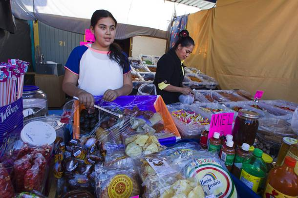 Daniela Madrigal Ocampo, 11, and her mother Maria Ocampo sell food items from their booth at the Broadacres Marketplace & Events Center Sunday Nov. 3, 2013.