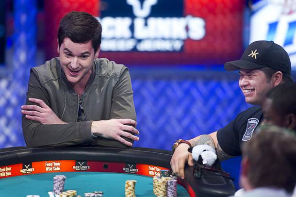 David Benefield, left, 27, a part-time student and part-time poker professional from New York City, reacts after going
