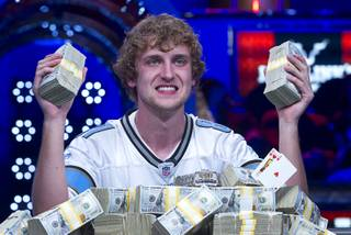 Ryan Riess, 23, a poker professional from East Lansing, Mich., poses with stacks of cash after winning the World Series of Poker $10,000 buy-in no-limit Texas Hold 'Em tournament at the Rio Tuesday, Nov. 5, 2013.