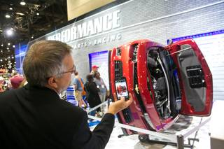 Ralph Marciano, of Rhode Island, takes a photo of a Chevrolet Camaro that has been lifted on to its side during the 2013 SEMA show at the Las Vegas Convention Center, Tuesday, Nov. 5, 2013.