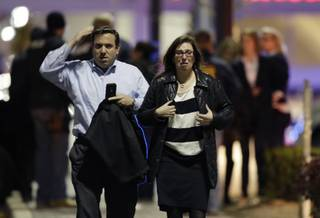 A man and woman leave the Garden State Plaza Mall with officials standing guard behind them following reports of a shooter, Monday, Nov. 4, 2013, in Paramus, N.J. Hundreds of law enforcement officers converged on the mall Monday night after witnesses said multiple shots were fired there.