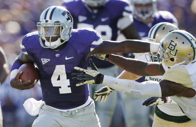 Kansas State quarterback Daniel Sams (4) stiff-arms his way past Baylor safety Ahmad Dixon, right, during the first half of an NCAA college football game in Manhattan, Kan., Saturday, Oct. 12, 2013.