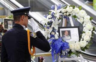 TSA officer Fritz Corros salutes at Los Angeles International Airport, during a moment of silence Friday Nov. 8, 2013, to honor the Transportation Security Administration officer Gerardo Hernandez, killed by a gunman at the airport a week ago.