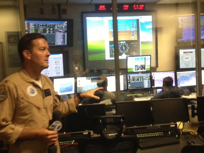A Global Hawk pilot explains how the control room for unmanned aerial systems at NASA's Dryden Flight Research Center at Edwards Air Force Base works. Pilots use a joystick or mouse to fly drones.
