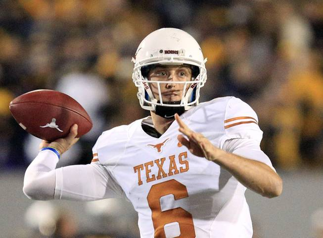 Texas quarterback Case McCoy finds an open receiver late in the fourth quarter during an NCAA college football game against Texas in Morgantown, W.Va., on Saturday, Nov. 9, 2013. Texas won 47-40 in overtime.