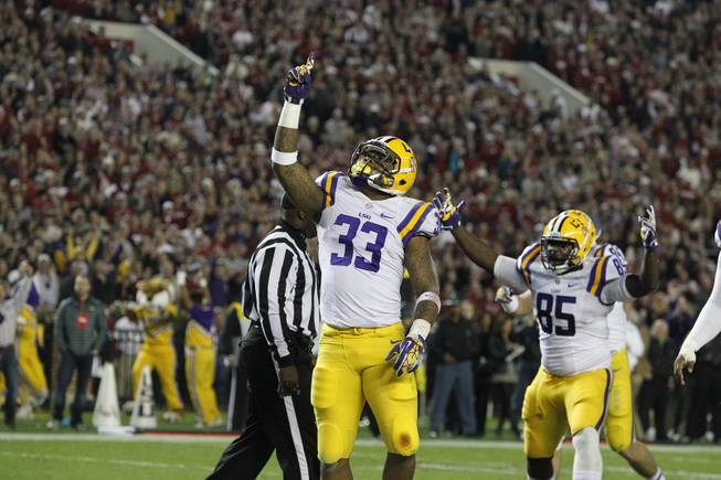 LSU running back Jeremy Hill (33) celebrates his touchdown against Alabama during the first half of an NCAA college football game, Saturday, Nov. 9, 2013, in Tuscaloosa, Ala.