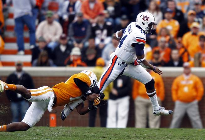 Auburn quarterback Nick Marshall (14) tries to get away from Tennessee linebacker Brent Brewer (17) in the third quarter of an NCAA college football game on Saturday, Nov. 9, 2013 in Knoxville, Tenn.