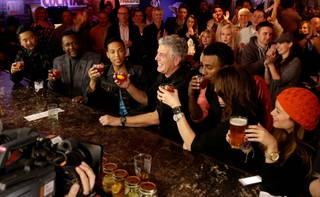 "Anthony Bourdain, third from right, films his CNN series ""Parts Unknown"" with chef Roy Choi, actor Wendell Pierce, CNN anchor Don Lemon, chef Marcus Samuelsson and comedienne Bonnie McFarlane at Atomic Liquors on Sunday, Nov. 10, 2013, in downtown Las Vegas. The woman at right was not part of the filming."